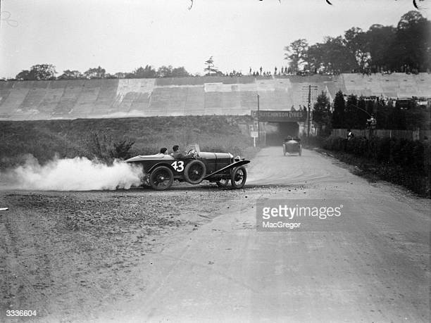 100 miles high speed reliability trials by the Junior Car Club at Brooklands Weybridge Surrey England A competitor negotiating one of the hairpin...