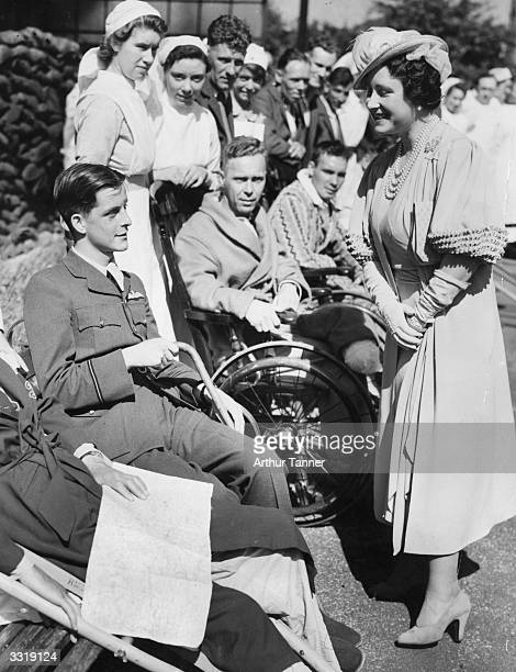 Queen Elizabeth Queen Consort to King George VI talking to a wounded RAF officer during a visit to Wellhouse Hospital Barnet London administered by...