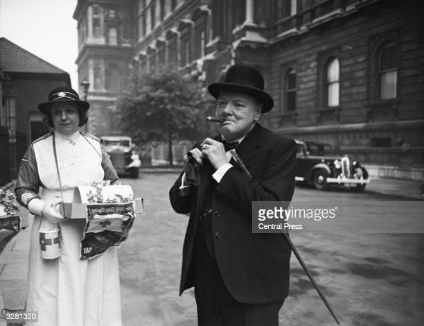 Winston Churchill pins his flag into his lapel after he had bought one in aid of Red Cross Day in London