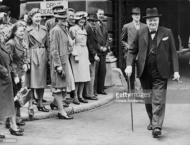 Government workers in Downing Street, London, cheering Winston Churchill on his return to London from America.