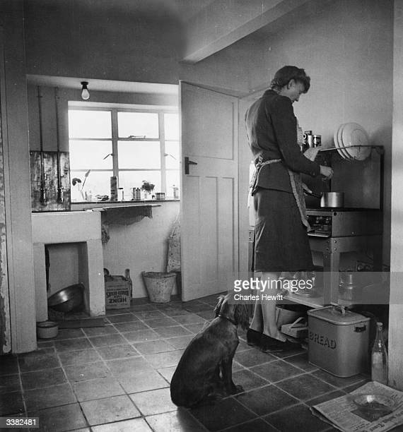 The wife of architect's draughtsman Brian Wilkinson cooking in the kitchen of their homemade home a converted barn and cowshed in East Wittering near...