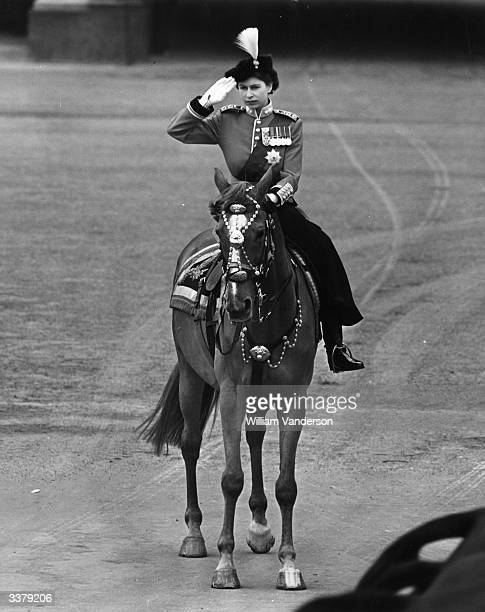 Queen Elizabeth II riding a horse side saddle and saluting during a Trooping of the Colour ceremony at Horse Guard's Parade Central London