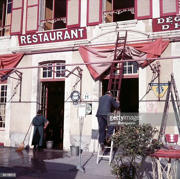 The front of a restaurant is cleaned in CoursellesSurMer the town where ten years earlier in 1944 General de Gaulle landed during the Normandy...