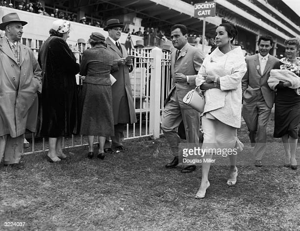 British-born actress Elizabeth Taylor and her husband, film producer Mike Todd , attend Derby Day at Epsom with singer Eddie Fisher and his wife...