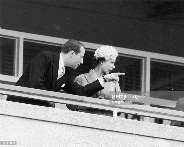 Lord Porchester points out an item of interest to Her MajestyThe Queen in the Royal Box at Epsom