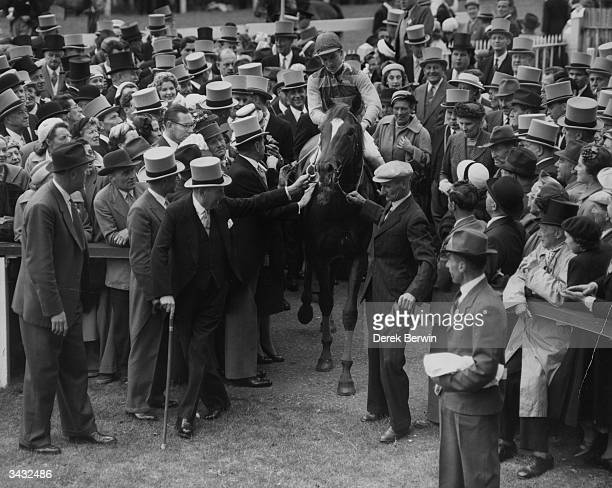 Surrounded by a crowd of wellwishers winning owner Sir Victor Sassoon helps to lead jockey Lester Piggott on 'Crepello' into the unsaddling enclosure...