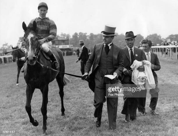 Jockey Lester Piggott on 'Petite Etoile' is led in by Prince Ali Khan after winning the 1959 Oaks Stakes on Ladies' Day at Epsom