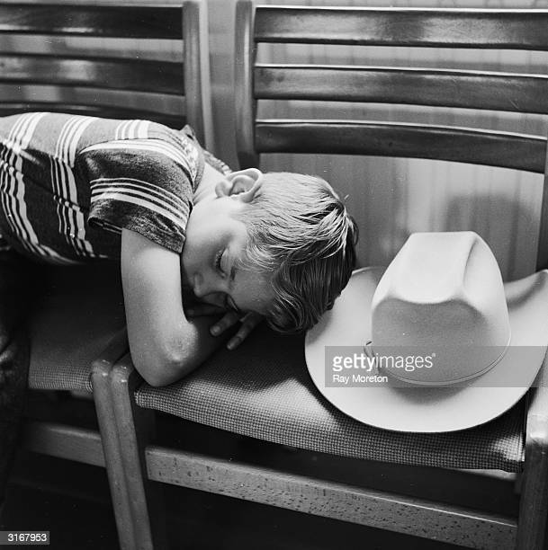 Ten yearold Raymond Held fast asleep by his ten gallon hat after playing the changeling boy in a production of 'A Midsummer Nights Dream' at a School...