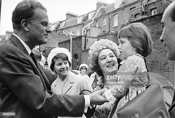 American evangelist Billy Graham shakes hands with a little girl during a visit to Britain