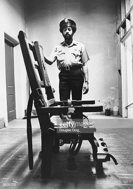 US Correction Officer Willie Davis stands behind the electric chair in the Death House at State Prison New Jersey