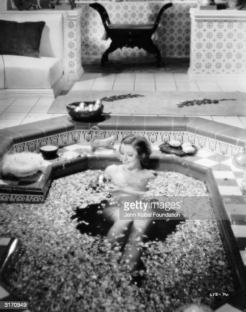 Hollywood actress Myrna Loy luxuriates in a sunken bath in a racy scene from 'The Barbarian' a desert romance directed by Sam Wood