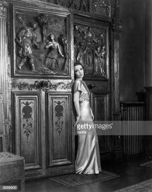 American actress Bessie Love standing by an ornately carved door in her London home She is currently touring England with her new revue 'Lucky Stars'