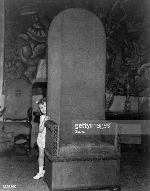 Peering round a large high backed tapestry covered chair in her mother's London home is Patricia young daughter of American actress Bessie Love who...