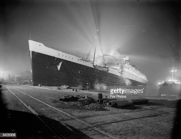 The newly completed SS Queen Mary flloodlit at night at the shipyard on Clydebank Scotland