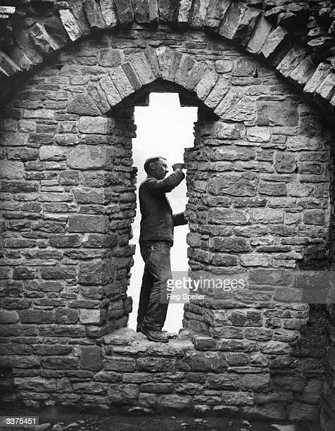 A builder restoring stonework on one of the arches of the West Tower of the 12th century Norman built Newport Castle in south Wales The whole of the...