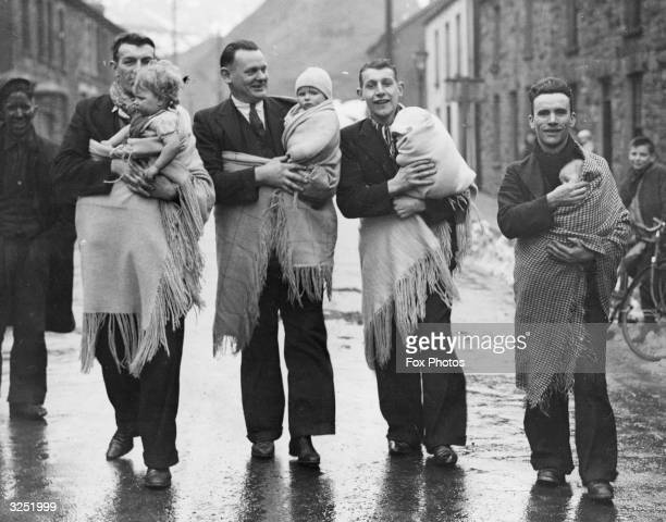 Fathers at Blaenrhondda, South Wales, taking their babies out for some fresh air. Rather than use a pram, the custom is to wrap the child in a shawl.