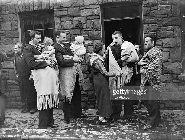 Fathers in Blaenrhondda south Wales prepare to take their babies out for a walk as is the custom in the area The men carry their children in large...
