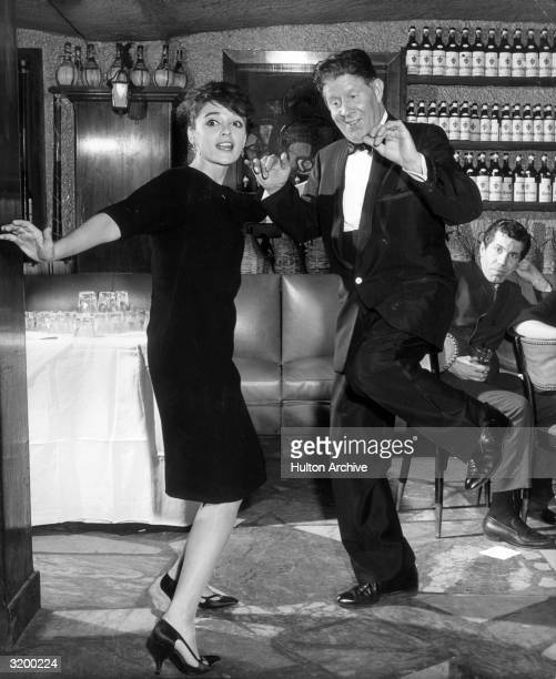 A portrait of singer Anna Maria Alberghetti dancing the Twist with Rudy Vallee at a party at Leone's to celebrate Alberghetti's first year as an...