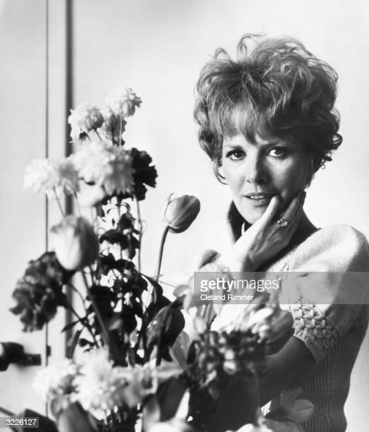 Pop singer Petula Clark posing next to a bunch of flowers.
