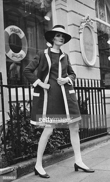 Model Claire Ferson wears the Dior cardigan look a navy dress coat and matching hat all trimmed with white