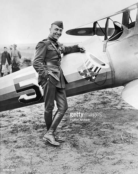 American aviator and lieutenant Eddie Rickenbacker dressed in uniform stands next to his World War I plane in a field near Toul France The plane is...