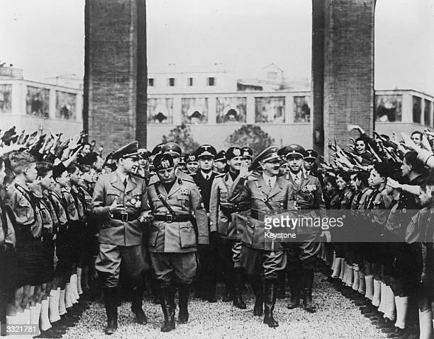 German dictator Adolf Hitler and Italian prime minister Benito Mussolini arrive at Massenzio Hall, Rome. They are welcomed and saluted by supporters,...