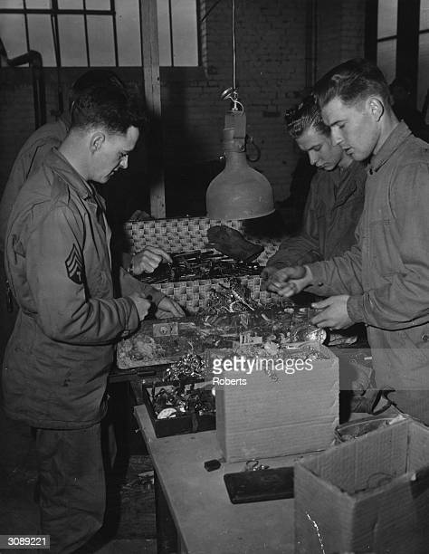 American soldiers sorting and examining jewellery taken from victims in the Buchenwald concentration camp