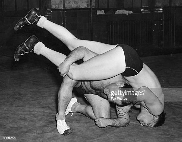 Two of Britain's wrestlers train for the Olympics at Islington. Kneeling is Fred Oberlander a previous British heavy champion. His challenger, L...