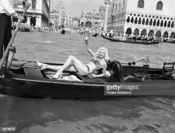British actress Diana Dors wearing a mink bikini whilst riding in a Gondola by St Mark's Square Venice during the Venice film festival