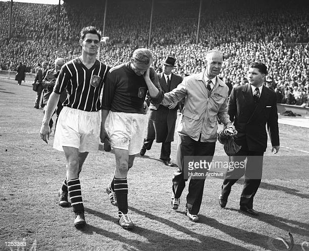 FA Cup Final Birmingham City v Manchester City After helping Manchester City win the Cup 31 Bert Trautmann injured during the match is helped off the...