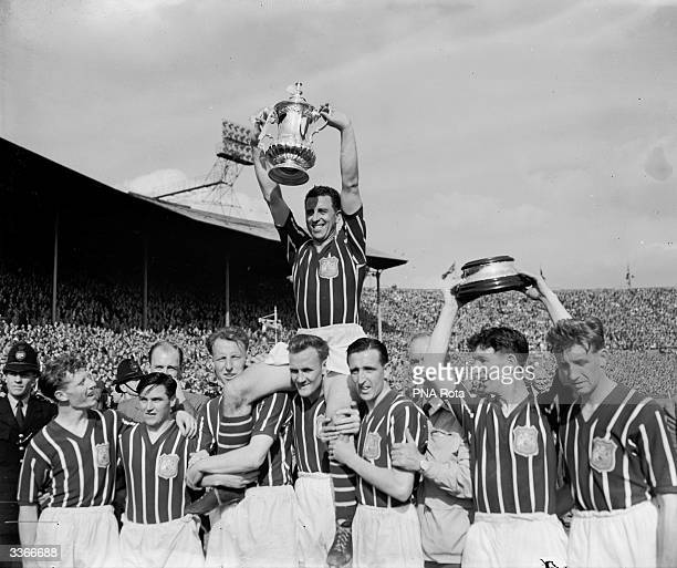 Manchester City captain Roy Paul holds the FA Cup aloft in victory as his team mates bear him in a victory lap after their 31 win over Birmingham...