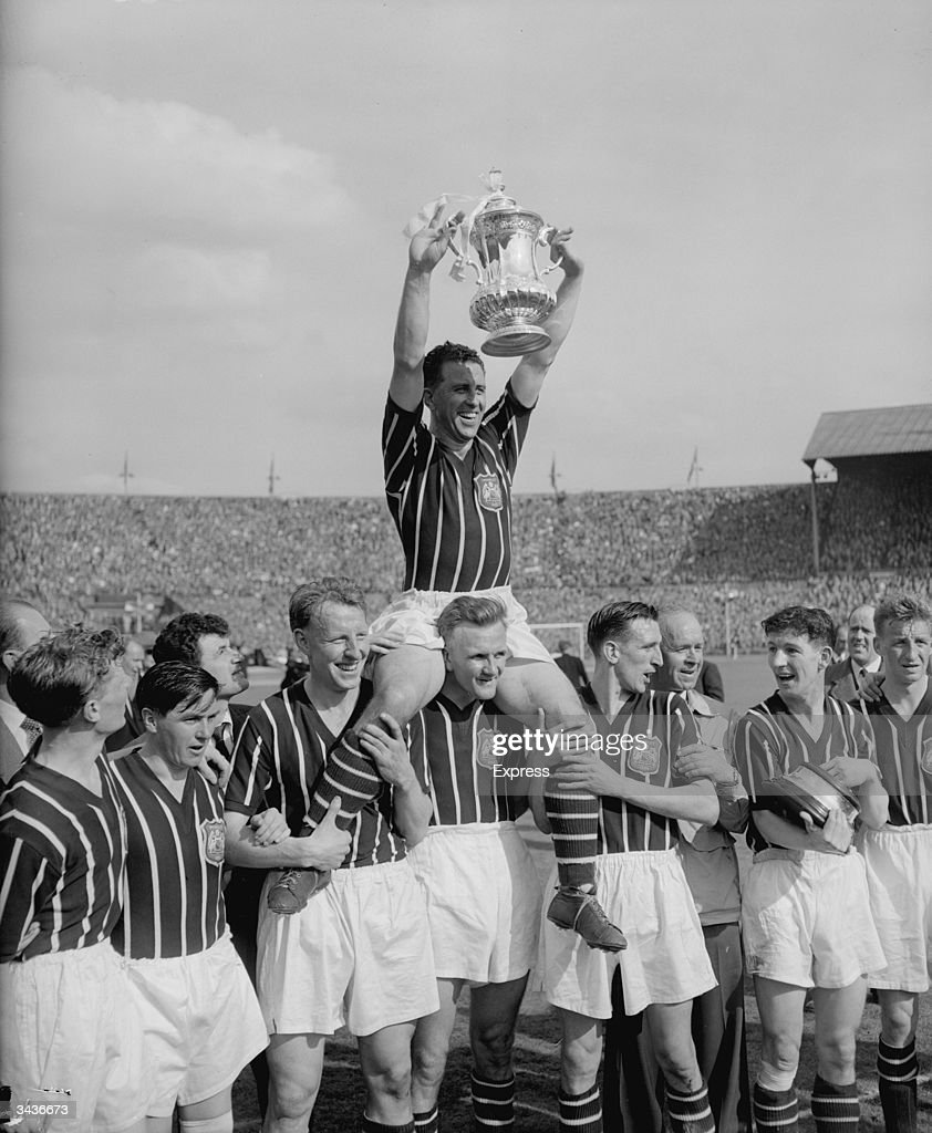 Manchester City captain Roy Paul is chaired by goalkeeper Bert Trautmann after Manchester City's 3-1 victory against Birmingham City in the FA Cup Final at Wembley Stadium.
