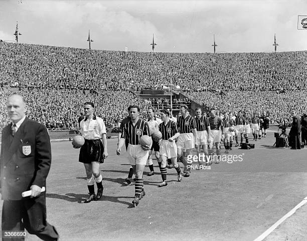 The team captains of Manchester City and Birmingham City lead their players onto the field at Wembley London before the FA Cup Final match