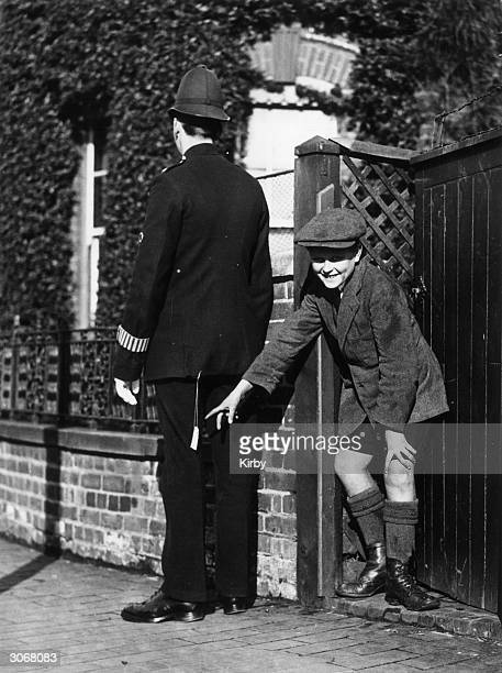 A young boy plays a practical joke on a policeman with a rickrack firework attached to his jacket