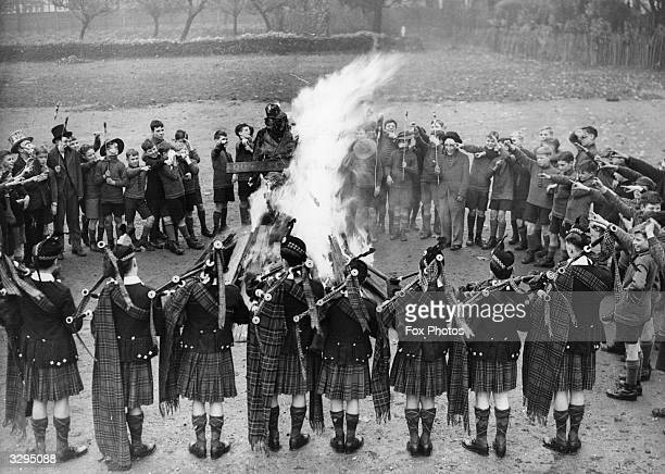 The boys of the Dr Barnardo's home in Kingston celebrating Guy Fawkes with the school pipers playing a lament while the Guy goes up in flames