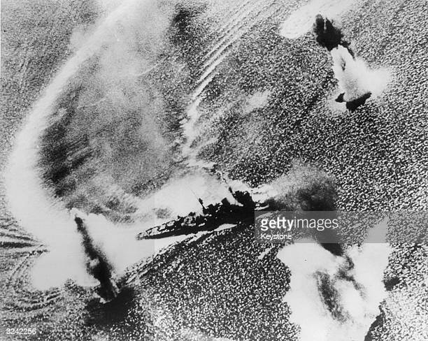 A Japanese cruiser in Manila Bay off the Philippines leaves a frantic wave as she tries in vain to avoid the rain of bombs aimed at her by...