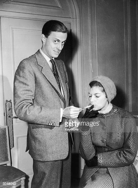 Baron Baron Hans Heinrich von Thyssen-Bornemisza lights a cigarette for his new wife, British fashion model Fiona Campbell-Walter, whilst staying at...