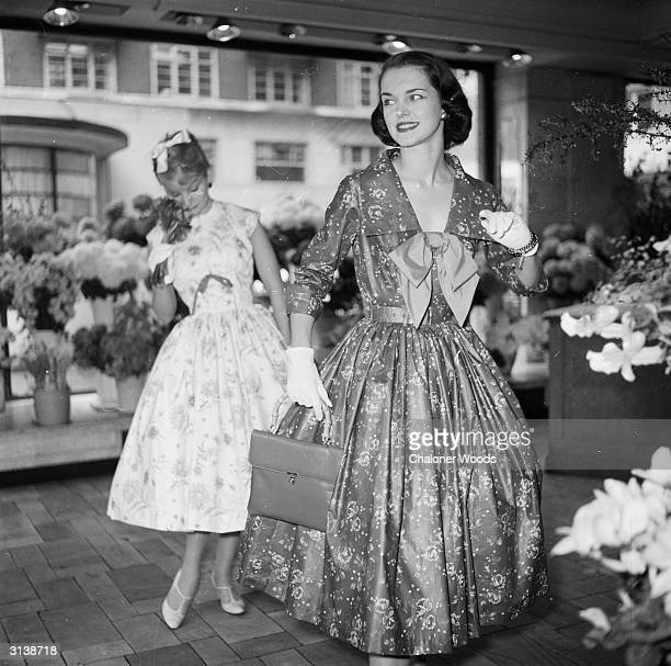 Two prim young debutantes wearing floral knee-length ball-gowns, loiter around a flower stall. Vanity Fair