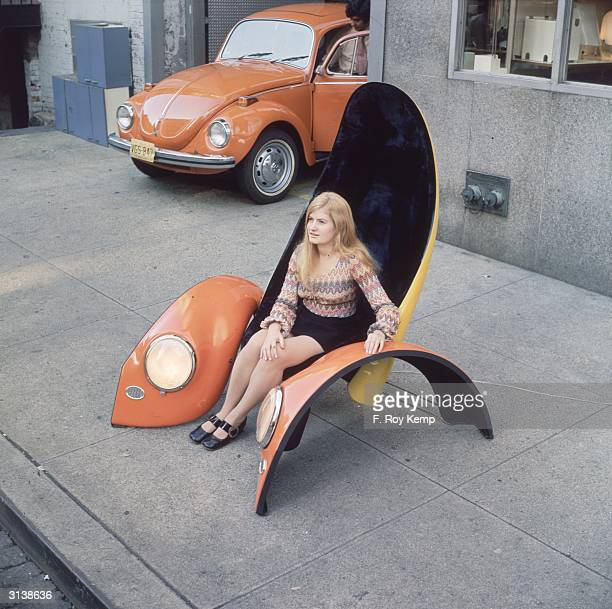A model demonstrates a recliner chair made from the bonnet of a Volkswagen Beetle