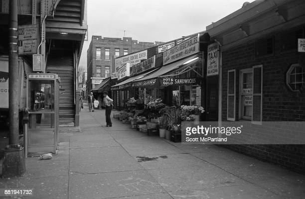 A lady exits a fruit and vegetable stand below the elevated subway line on Roosevelt Avenue in the heart of Corona Queens