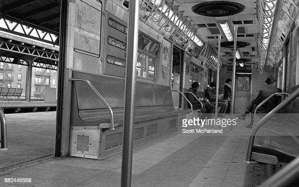 A subway train sits with it's doors open at the 82nd Street subway station in Corona Queens as commuters enter and sit down
