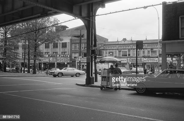 Street level view of The Plaza Movie Theater and other small businesses along Roosevelt Avenue in Corona Queens from underneath the elevated subway...
