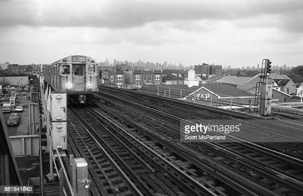 The number Seven Train pulls into the elevated subway station at 103rd Street in Corona Queens with the New York City skyline visible in the...
