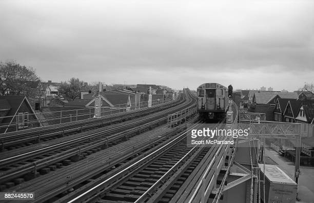 The number Seven Train travels along the elevated subway tracks through a residential neighborhood in Corona Queens