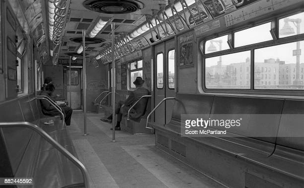 Three commuters sit in a graffiti covered subway car as it travels through Corona Queens