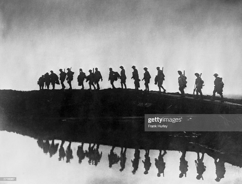 Supporting troops of the 1st Australian Division walking on a duckboard track near Hooge, in the Ypres Sector. They form a silhouette against the sky as they pass towards the front line to relieve their comrades, whose attack the day before won Broodseinde Ridge and deepened the Australian advance.