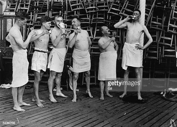 Hiding their modesty with towels members of the 7 o'clock Regulars Swimming Club Plymouth inaugurate the winter season by drinking from trophies they...