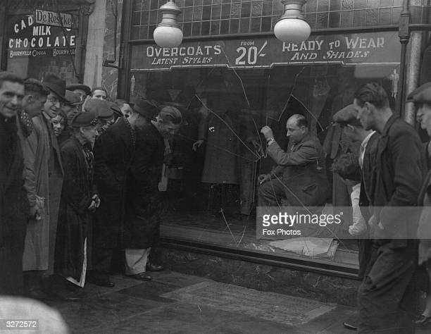 A group of people inspect the damage to a clothing shop window which was smashed by antisemitic gangs in East London