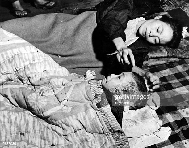 Mother tends her injured child, a victim of the 6th August atomic bomb attack on Hiroshima.