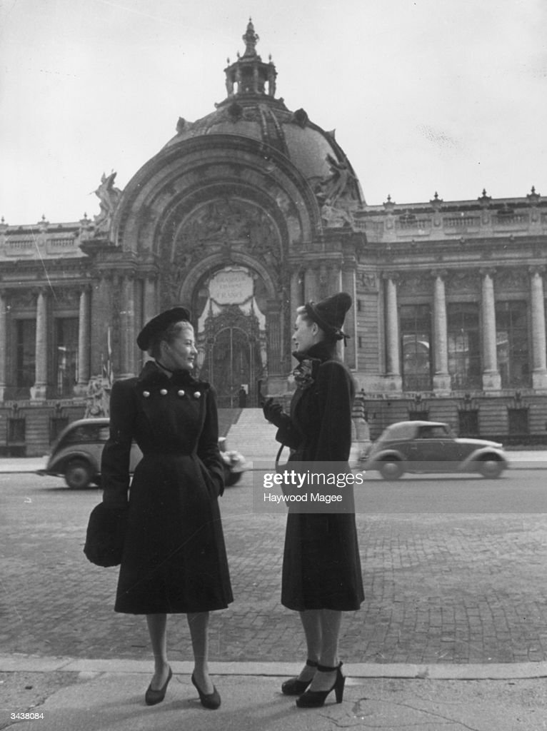 Two models pose in the street in coats by Piguet, Paris. One model's shoes have peep-toes, ankle-straps and sling-backs. Original Publication: Picture Post - 4222 - Backstage at a Dress Show - pub. 1946